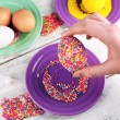 Female hand with decorated Easter egg with colorful beads on wooden table, closeup — Stock Photo #70235393