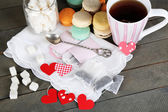 Heart shaped teabag tags, macaroons and cup of tea on wooden background — Stock Photo