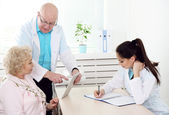 Happy doctors and patient in hospital clinic — Stock Photo