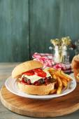 Tasty burger and french fries on plate, on wooden background. Unhealthy food concept — Stock Photo
