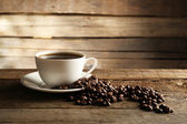 Cup of coffee with grains on wooden background — Fotografia Stock