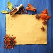 Different kinds of spices on paper sheet on wooden background — Stock Photo