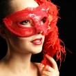 Portrait of beautiful woman with fancy glitter makeup and masquerade mask on dark background — Stock Photo #70600073
