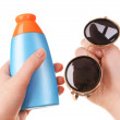 Bottle of suntan cream and sunglasses in female hands isolated on white — Stock Photo #70600191