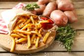 Tasty french fries on cutting board, on wooden table background — Stock Photo