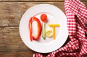 Word DIET made of sliced vegetables in white plate on wooden table, top view — Stock Photo