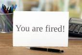Message You're Fired on wooden table, closeup — Stock Photo