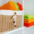 Colorful towels with wicker basket on shelf of rack background — Stock Photo #70793125