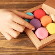 Female hand taking tasty colorful macaroons from present box on rustic wooden planks background — Fotografia Stock  #70795671