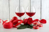 Composition with red wine in glass, red roses and decorative heart on color wooden background — Stock Photo