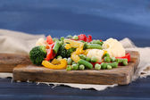 Frozen vegetables on cutting board, on napkin, on wooden table background — Stock Photo
