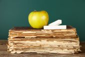 Old books, apple and chalk on blackboard background — Stock Photo
