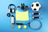 Sports equipment and T-shirt on color table, top view — Stock Photo