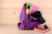Gun in school backpack — Stock Photo