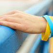 Hand with blue-yellow bracelet - colors of flag of Ukraine — Stock Photo #71129581
