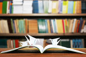 Open book with paper cranes on bookshelves background — Photo