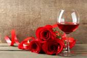 Composition with red wine in glasses, red roses and decorative heart on wooden background — Stock Photo