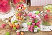 Multicolor candies in glass jars on wooden background — Stock Photo