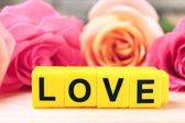 Beautiful roses with word LOVE — Stock Photo