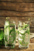 Glasses with fresh organic cucumber water on wooden table — Stock Photo