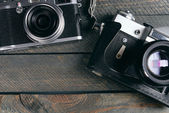 Old retro cameras on rustic wooden planks background — Stock Photo