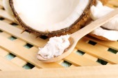 Fresh coconut flesh in wooden spoon on wooden grid background — Stock Photo