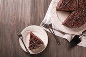 Plátky lahodný čokoládový dort s příbory na dřevěný stůl pozadí — Stock fotografie