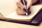 Female hand writing in diary by pen on wooden table background — Stockfoto