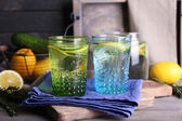 Fresh water with lemon and cucumber in glassware with napkin on wooden table, closeup — Foto de Stock