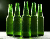 Glass bottles of beer on dark background — Stock Photo