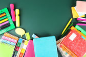 Bright school supplies on blackboard background — Stock Photo