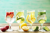 Glasses of different home made freshness healthy vitamin-fortified water on wooden table — Stock Photo