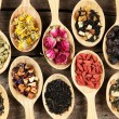 Collection of tea and natural additives in wooden spoons, on old wooden table — Stock Photo #71142051