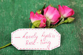 Beautiful rosy twig with tag on wooden background — Stockfoto