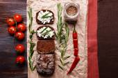 Bread with cottage cheese, greens and tomatoes on paper on table top view — Stock Photo