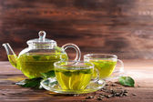Cups of green tea on table on wooden background — Stock Photo
