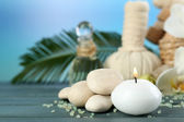 Still life with candle, pebbles and  spa treatment on wooden table, on bright background — Foto de Stock