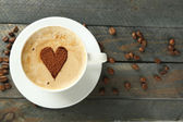 Cup of cappuccino with heart of cocoa on wooden table — Stock Photo