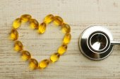 Heart of cod liver oil and stethoscope, on wooden background — Stock Photo