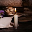 Still life with retro books and candlelight on wooden table, closeup — Stock Photo #71224257
