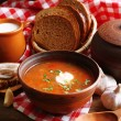 Ukrainian beetroot soup - borscht in bowl and pot, on napkin, on wooden background — Stock Photo #71221903