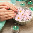Female hands with bowl of aroma spa water on wooden table, closeup — Stock Photo #71225511