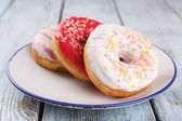 Delicious donuts with icing on plate on wooden background — Stock Photo