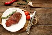 Composition with tasty roasted meat on plate, tomatoes and rosemary sprigs on wooden background — Stock Photo