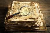 Grunge papers with hieroglyphics with magnifier on wooden background — Stock Photo