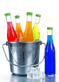 Bottles of tasty drink in metal bucket with ice isolated on white — Stockfoto