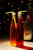 Alcoholic cocktails in glass bottles with straws on dark bright background — Stock Photo