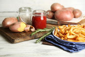 Tasty french fries on plate, on wooden table background — Stock Photo