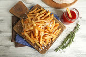 Tasty french fries on cutting board, on wooden table background — Foto de Stock