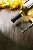 Bottle of wine with grape and corkscrew on wooden background — Stock Photo